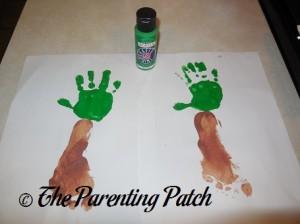 Green Handprints Above Brown Footprints
