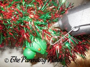 Hot Gluing the Christmas Garland to the Straw Wreath