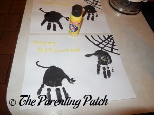 Using Yellow Paint to Paint on the Cat's and Spiders Eyes and Happy Halloween