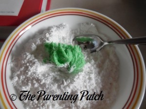 Rolling the Grinch Cookie Dough in Powdered Sugar and Corn Starch
