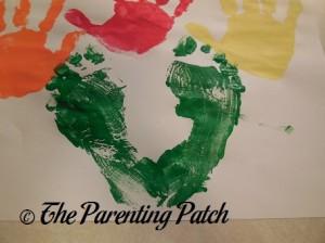 Two Green Footprints Under Handprints
