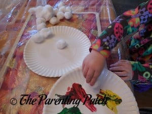 Toddler Gluing Cotton Balls on a Paper Plate