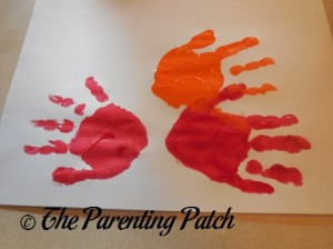 One Orange Handprint and Two Red Handprints