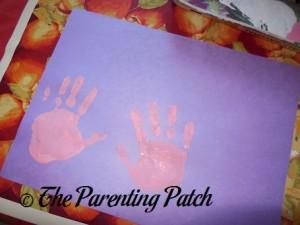 Pink Handprints on Purple Construction Paper