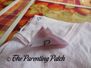 Marking the Family Cloth with the Letter P