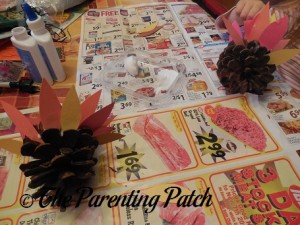 Gluing the Construction Paper Ovals to the Pinecones