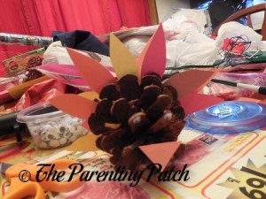 Gluing an Orange Construction Paper Triangle to the Pinecone