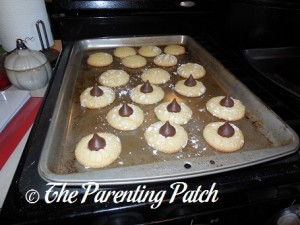 Adding the Chocolate Kisses to the Butter Cake Blossom Cookies