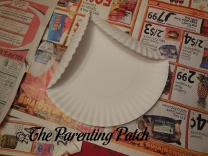 Folding the Sides of the Paper Plate for Paper Plate Penguin Craft