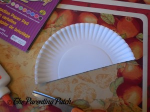 Cutting the Paper Plate in Half for the Pot of Gold Rainbow Paper Plate Craft