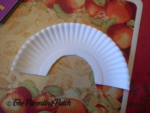 Cutting the Paper Plate into an Arch for the Pot of Gold Rainbow Paper Plate Craft