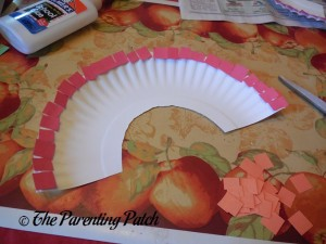 Gluing Red Squares on the Pot of Gold Rainbow Paper Plate Craft
