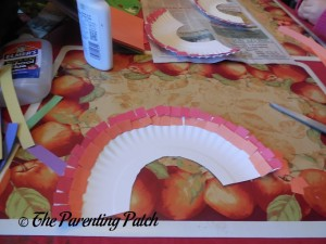 Gluing Orange Squares on the Pot of Gold Rainbow Paper Plate Craft
