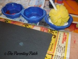 Dipping the Foam Dish Brush in Blue, White, and Red Acrylic Paint