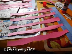 Gluing the Red Wiggly Strips onto a Wide Blue Panel