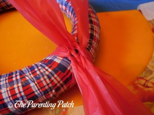 Tying Red Tablecloth Strips for Patriotic Wreath Craft