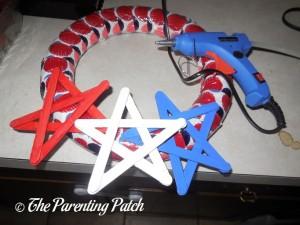 Gluing Stars on Patriotic Craft Stick Star Wreath