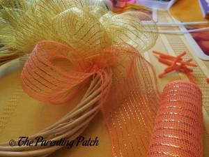 Attaching Orange Deco Mesh to the Deco Mesh Candy Corn Wreath Craft