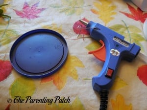 Plastic Lid and Hot Glue Gun for Patriotic Rolled Paper Wreath Craft