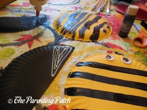 Gluing Black Wings on the B Is for Bumblebee Paper Plate Craft
