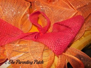 Adding Red Burlap Ribbon to the Deco Mesh and Burlap Ribbon Autumn Wreath Craft