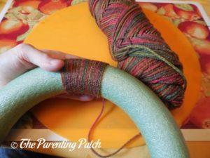 Wrapping Yarn Around Autumn Pumpkin Yarn Wreath Craft