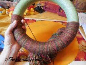 Wrapping More Yarn Around Autumn Pumpkin Yarn Wreath Craft