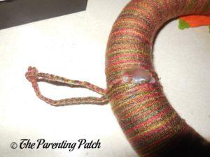 Attaching Braid to Autumn Pumpkin Yarn Wreath Craft