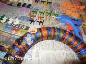 Gluing Decorations to Halloween Yarn Wreath Craft