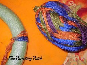 Wrapping Yarn Around Halloween Ribbon and Yarn Wreath Craft