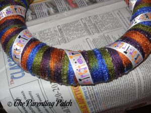 Wrapping More Ribbon Around Halloween Ribbon and Yarn Wreath Craft