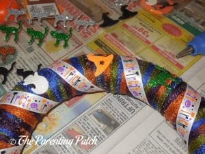 Gluing Decorations to Halloween Ribbon and Yarn Wreath Craft