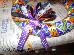 Gluing Ribbon Around Ribbon Bow on Duct Tape Halloween Wreath Craft