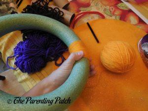 Wrapping Yarn Around Halloween Yarn Block-Color Wreath Craft