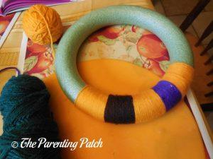 Wrapping More Yarn Around Halloween Yarn Block-Color Wreath Craft