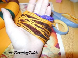 Wrapping Yarn Around Hand for Halloween Yarn Block-Color Wreath Craft