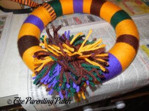 Gluing Decorations to Halloween Yarn Block-Color Wreath Craft