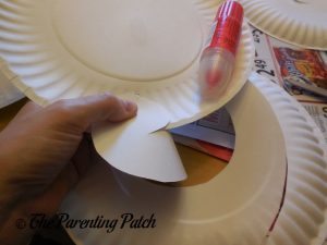 Gluing the Spiral on the G Is for Ghost Halloween Paper Plate Craft