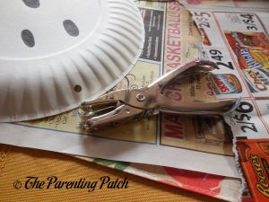 Punching a Hole for the G Is for Ghost Halloween Paper Plate Craft