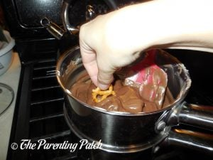 Dipping a Pretzel in Melted Chocolate Almond Bark