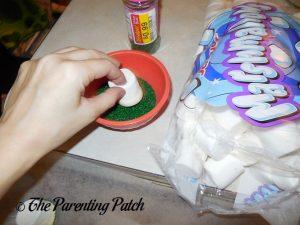 Dipping a Marshmallow in Green Sugar
