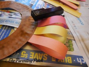 Stapling Folded Paper Strips on the Turkey Paper Plate Wreath Craft
