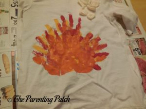 White Shirt with Red, Yellow, and Orange Handprints