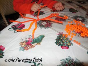 Threading Beads on Pipe Cleaners for Pony Bead Pumpkin Craft