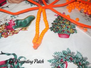 Twisting Beaded Ends of Pony Bead Pumpkin Craft