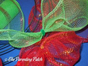 Adding Green Deco Mesh to the Deco Mesh Christmas Wreath Craft