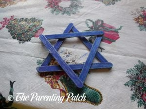 Coloring the Star Blue for the Star of David Hanukkah Ornament Craft