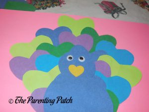 Gluing Eyes on the Heart Peacock Valentine's Day Craft