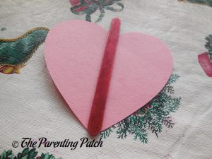 Gluing the Craft Stick on the Heart for the Love Bug Valentine's Day Craft