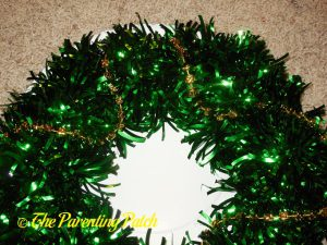 Adding Gold Beads to Green Tinsel Mardi Gras Wreath